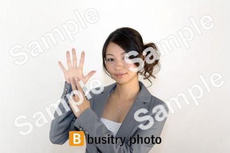 指で7のポーズをする女性