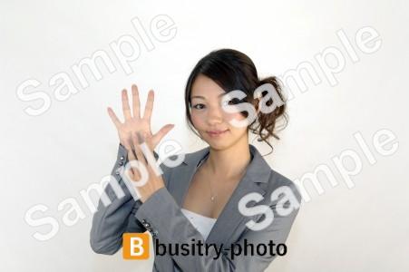 指で8のポーズをする女性