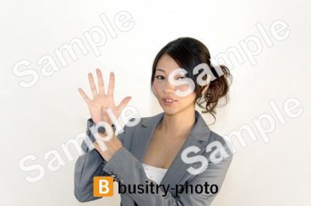 指で6のポーズをする女性