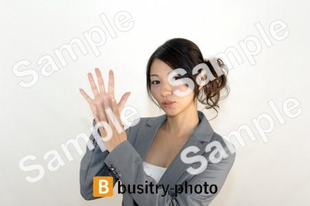 指で9のポーズをする女性