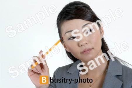鉛筆で頭を掻く女性