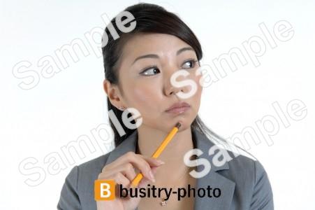 顎に鉛筆を当てる女性
