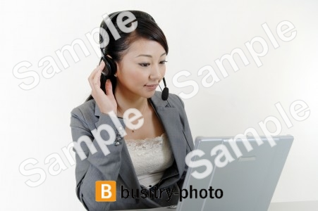 ヘッドセットをつけてパソコンをする女性