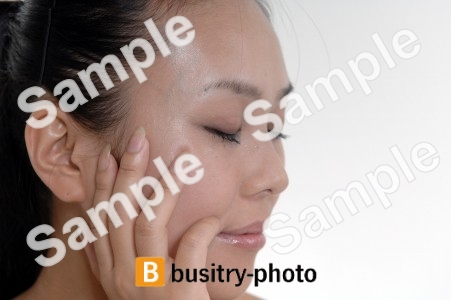 頬に手を当てて目を閉じる女性