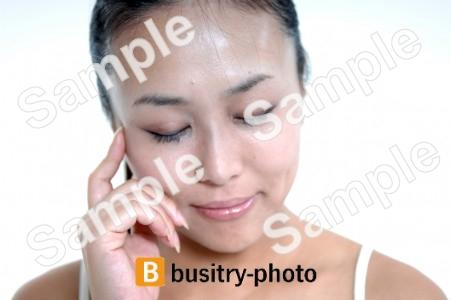 頬に指を当てる女性