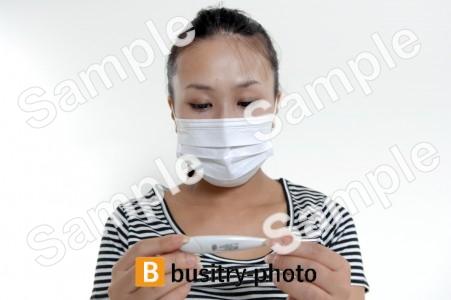 体温計を使うマスクをつけた女性