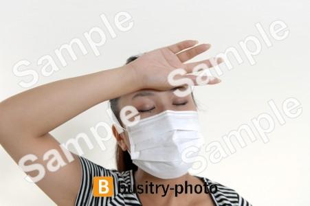 手で熱を測るマスクをつけた女性