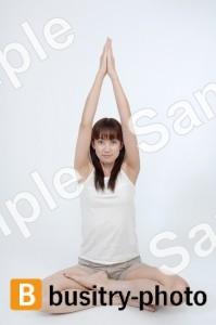 あぐらをかきながら手を上に伸ばす女性