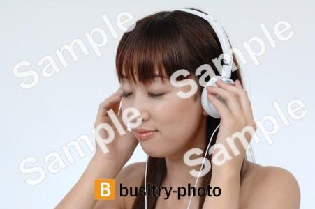 ヘッドホンをつけて音楽を聴く女性