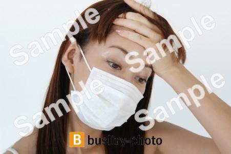 頭痛を気にするマスクをつけた女性