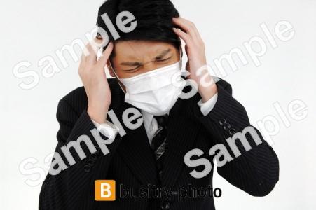 頭を抱えるマスクをつけた男性