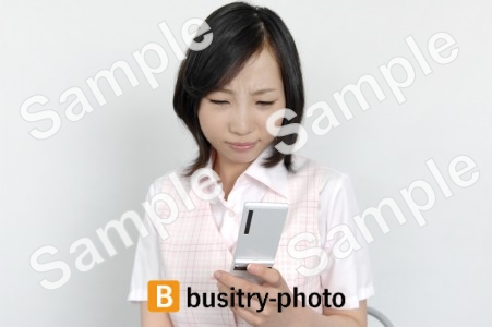 携帯電話でメールする女性
