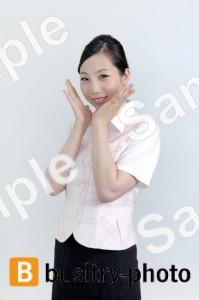 両手を顔の横で広げる女性