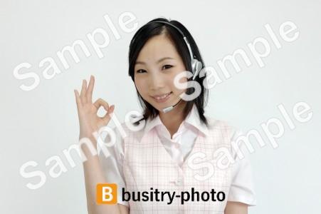 指でオッケーマークをするヘッドセットをつけた女性