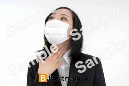 のどを触るマスクをつけた女性
