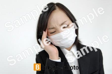 頭を抱えるマスクをつけた女性