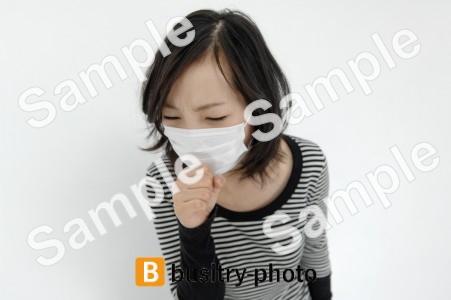 マスクをつけた咳き込む女性