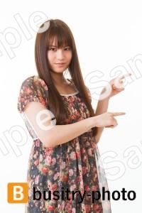 横を指差す女性