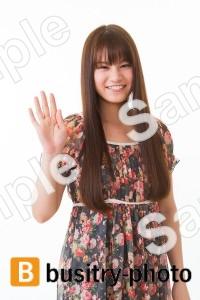 片手を挙げる女性