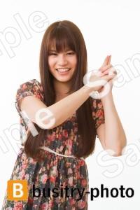 手で拳銃のポーズをする女性