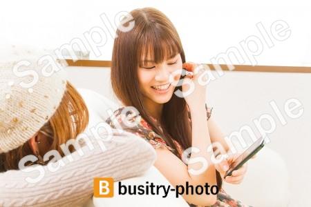友人にスマホを見せる女性