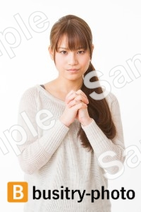 胸の前で手を合わせる女性