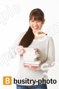 本の山を手にする女性