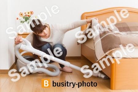 ベッドの下を掃除する女性