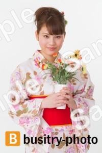 花を持つ着物姿の女性