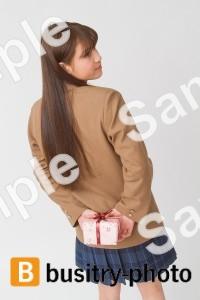 プレゼントを後ろで隠す女子高生