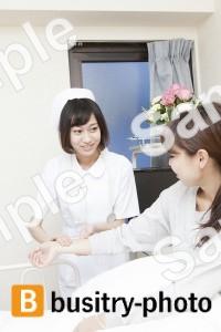 女性患者の脈を測る看護師