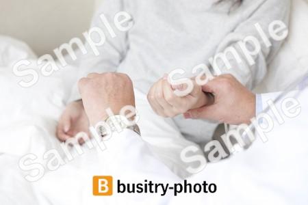 女性患者の脈を測る医師