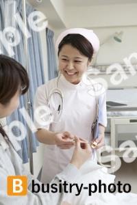 看護師に体温計を渡す女性患者