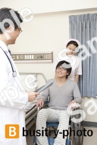 車椅子に乗る男性患者と医師と看護師