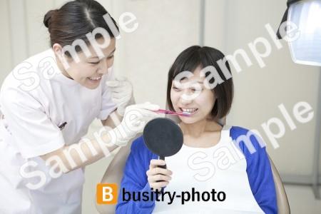 女性患者の歯を磨く歯科助手