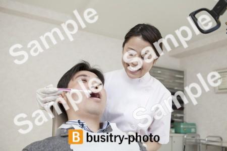 男性患者の歯を磨く歯科助手