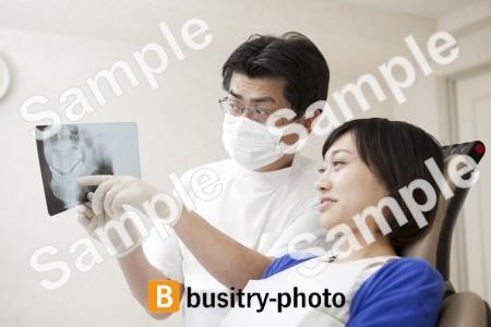 女性患者にレントゲンを説明する歯科医