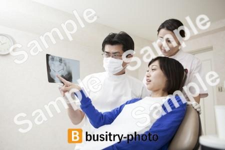 女性患者にレントゲンを説明する歯科医と歯科助手