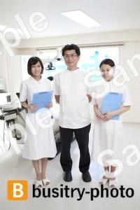歯科助手2人に挟まれる歯科医