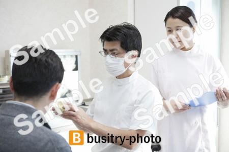 男性患者に説明をする歯科医と歯科助手