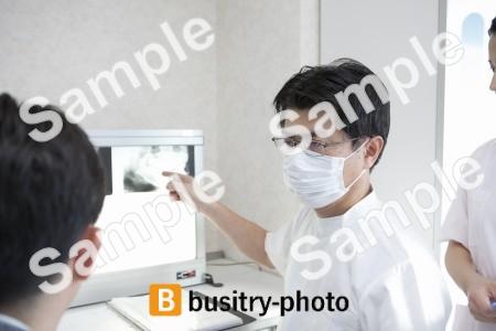 男性患者にレントゲンを説明をする歯科医