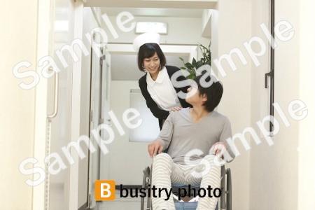 男性患者の車椅子を押す看護師