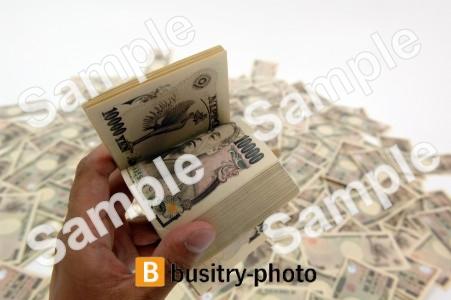 大量にばらまかれた一万円札と札束を数える手