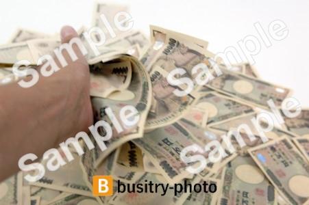 大量の一万円札をにぎる手